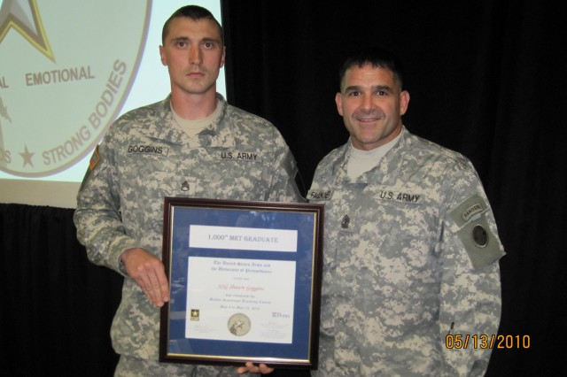 Staff Sgt. Shawn Goggins accepts a framed certificate from Sgt. Maj. Russel Faulkner