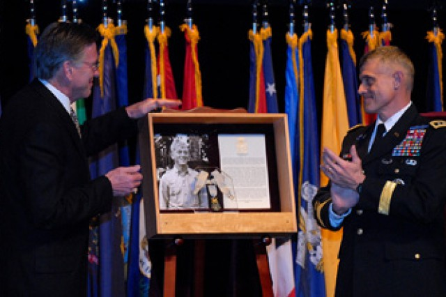 J. Kirk Davis, son of Hall of Fame inductee Charles Davis, pats the top of his father's Hall of Fame shadowbox containing the deceased colonel's Medal of Honor, after unveiling the box with Command and General Staff College Commandant Lt. Gen. Robert Caslen Jr. during the Hall of Fame induction ceremony May 11 in the Lewis and Clark Center's Eisenhower Auditorium, Fort Leavenworth, Kan.