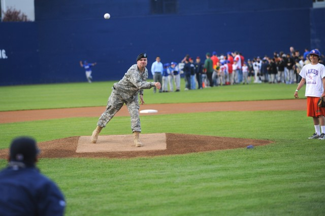Col. Thomas Brittain throws out the first pitch during the Tacoma Rainiers' Salute to Armed Forces night, Saturday. At right is Brittain's son, Thomas Brittain Jr.
