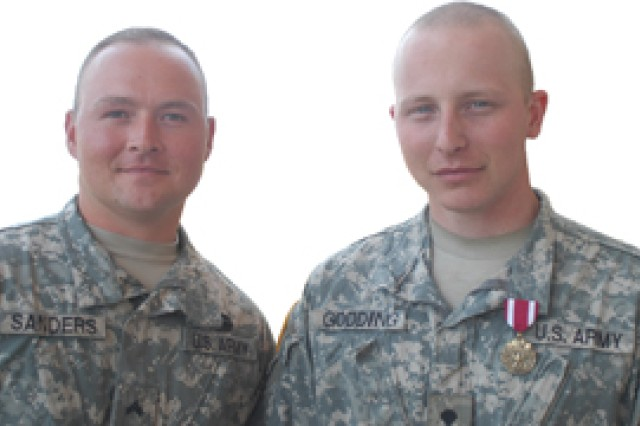 Cpl. Joe Sanders and Spc. Albert Godding pose April 27 after Godding received a Meritorious Service Medal for preventing Sanders' suicide in 2008.