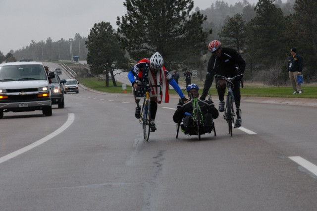 Navy Master Chief Petty Officer Will Wilson (left) and Warrant Officer Johnathan Holsey (right) encouraged  Sgt. Monica Southall to  keep going toward the finish line May 13, in a grueling Warrior Games cycling competition at the U.S. Air Force Academy.