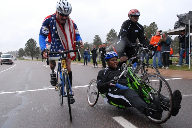 Left to right: Navy Master Chief Petty Officer Will Wilson, Sgt. Monica Southall and Warrant Officer Johnathan Holsey cross the finish line after a grueling Warrior Games cycling competition at the U.S. Air Force Academy May 13. After noticing Southall struggling to finish, Wilson and Holsey abandoned their race and remained with her to help her finish.