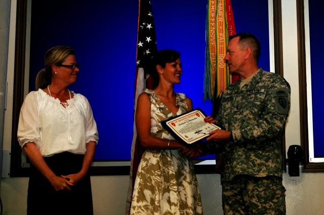 Sherri DeSilva, spouse of a Soldier assigned to Headquarters and Headquarters Company, 225th Brigade Support Battalion, 2nd Brigade Combat Team, 25th Infantry Division, receives an award for volunteering from Maj. Gen. Bernard S. Champoux, commanding general, 25th Inf. Div., and his wife, Mary Susan, during the division's Volunteer Recognition Ceremony May 13 at the Post Conference room, Schofield Barracks, Hawaii.