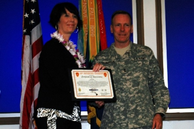 Dee Wafe, spouse of a Soldier assigned to 1st Battalion, 14th Infantry Battalion, 2nd Brigade Combat Team, 25th Infantry Division receives an award for volunteering from Maj. Gen. Bernard S. Champoux , commanding general, 25th Inf. Div., during the division's Volunteer Recognition Ceremony May 13 at the Post Conference room, Schofield Barracks, Hawaii.