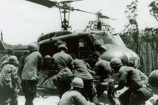 """Dust Off! This image shows wounded Troopers being loaded onto a UH1H Aca,!A""""HueyAca,!A? helicopter operating in a Aca,!A""""Dust OffAca,!A? or medical evacuation role.  Operation Apache Snow, May 1969. (Melvin Zais Photograph Collection)."""