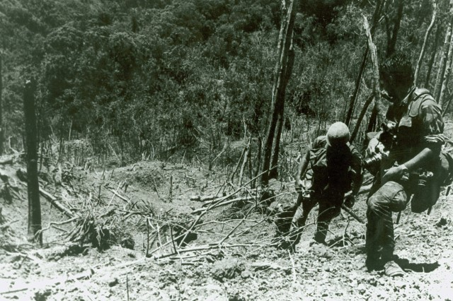 """Aca,!A""""1000 Words.Aca,!A? This image shows a U. S. Army Photographer and assistant climbing through the devastated landscape on Dong Ap Bia after the battle. (Melvin Zais Photograph Collection)."""