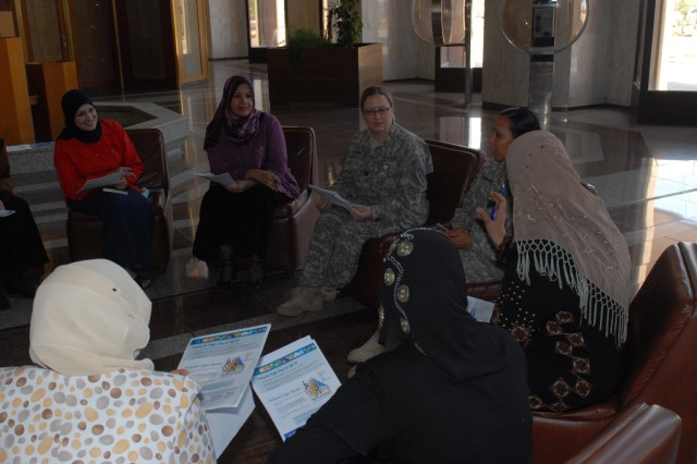 Capt. Tisha Bridge, 1st Infantry Division physician\'s assistant, and Spc. Aisha Bannat, an analyst with Division Headquarters and Headquarters Battalion, 1st Inf. Div., give a beginning English class to some women employees of the Basra International Airport May 5, 2010. The classes teach language skills, but also give the women an opportunity to discuss medical issues or concerns with Bridge.