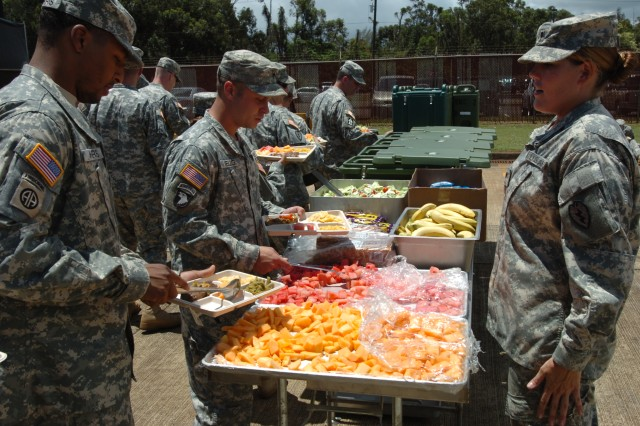 Spc. Caroline Thiel, a food service specialist assigned to Headquarters Support Company, 25th Special Troops Battalion, 25th Infantry Division, oversees the outside line as Soldiers from the unit serve themselves. The unit's cooks prepared lunch in a containerized kitchen in the battalion motor pool May 10 at Schofield Barracks, Hawaii.  (U.S. Army photo by Staff Sgt. Tim Meyer, 25th Inf. Div. Public Affairs.)