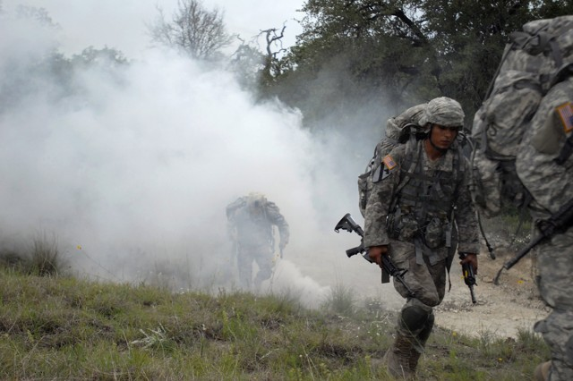 "FORT HOOD, Texas-Spc. Elias Luna moves tactically through smoke from a M18 smoke grenade to the next testing lane during 6th Squadron, 9th Cavalry Regiment's ""Spur Ride"", here, May 13."