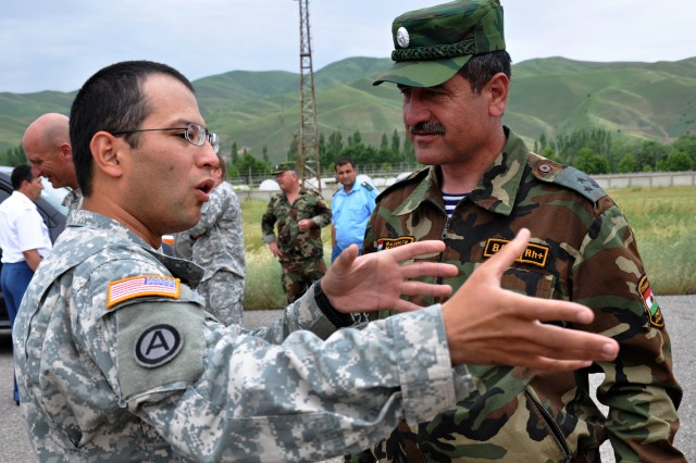 KULOB, Tajikistan--Spc. Saliyev Djamoliddin (left), a Third Army Soldier and native of Tajikistan, converses with a member of the Tajikistan Army at Kulob, Tajikistan May 16.  Djamoliddin expressed his pleasure with being able to come back to his home country and make a difference as a member of Third Army while helping the flood victims of Tajikistan.  (Photo by Staff Sgt. Dominic Hauser, Civil Military Operations Center).