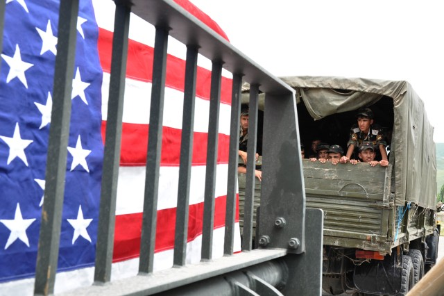 KULOB, Tajikistan -- Young soldiers in the Tajikistan Army look out the back of a truck as a pallet full of tents and covered with an American flag passes by.  Third Army Soldiers delivered over $250,000 worth of tents to Kulob, Tajikistan while answering the nation's call for help due to recent floods.  (Photo by Dominic Hauser, Civil Military Operations Center).