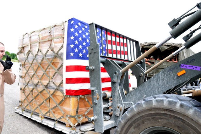 KULOB, Tajikistan--A pallet wrapped in an American flag full of tents is unloaded at an airfield near Kulob, Tajikistan May 16. The tents, part of U.S. aid to the flooded nation, were delivered to Tajikistan by Soldiers of Third Army and flown in via a C-17 Globemaster of the 21st Airlift Squadron. (Photo by Dominic Hauser, Civil Military Operations Center).