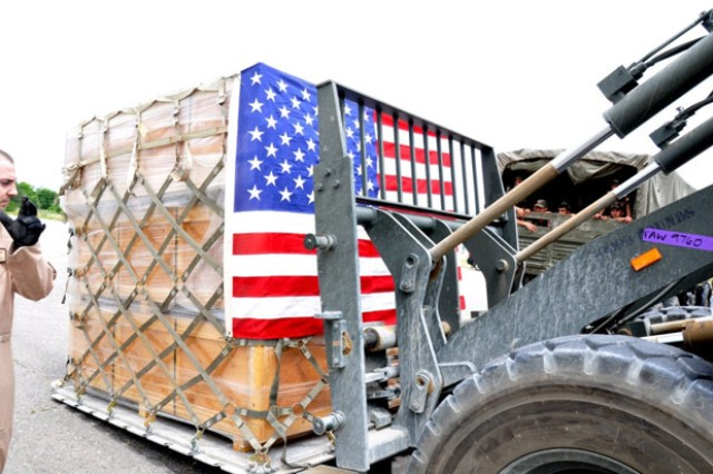 A pallet full of tents, wrapped in an American flag, is unloaded from a C-17 at an airfield near Kulob, Tajikistan, May 16.  The tents, part of U.S. aid to the flooded nation, were delivered to Tajikistan Soldiers.