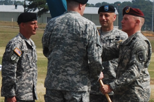 Brig. Gen. James C. Yarbrough, commander, Joint Readiness Training Center and Fort Polk, hands the 1st Maneuver Enhancement Brigade guidon to Col. David T. Theisen during the 1st MEB change of command ceremony at Honor Field May 12. Theisen takes command from his predecessor Col. Scott A. Spellmon (second from right).