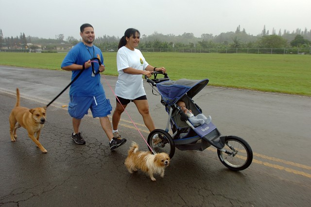 Carlos Badillo (left) and Staff Sgt. Evelyn Badillo, take their son, Carlos Badillo Jr. and their dogs Borzo and Daisy,a family competing in the 25th Infantry Division Equal Opportunity Asian Pacific American Heritage Month Run and Keiki Walk at Wheeler Army Airfield, May 15, walk at a moderate pace as the competition begins. The run celebrated the achievements of Asian-American and Pacific Islander citizens throughout the Nation's history and welcomed Soldiers and family to compete against one another for prizes. (U.S. Army photo by Spc. Jesus J. Aranda, 25th Infantry Division Public Affairs Office)