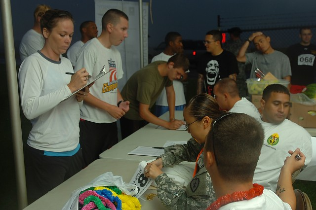 Karen Davenport (left), signs up for the 25th Infantry Division Equal Opportunity Asian Pacific American Heritage Month Run at Wheeler Army Airfield, May 15. The run, organized by the division's EO office, celebrated the achievements of Asian-American and Pacific Islander citizens throughout the Nation's history and welcomed Soldiers and family to compete against one another for prizes. (U.S. Army photo by Spc. Jesus J. Aranda, 25th Infantry Division Public Affairs Office)