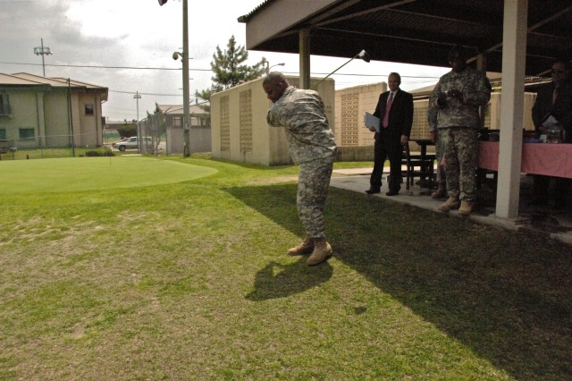 Maj. Gen. Reuben D. Jones (center), commanding general Family Morale, Welfare, and Recreation Command, tests a new golf club on the Indianhead Golf Course fairway during a visit to Casey Garrison's FMWR facilities May 13 while Chris Bradford (second from left), FMWR director and Col. Larry 'Pepper' Jackson (third from left), Red Cloud Garrison commander, look on.