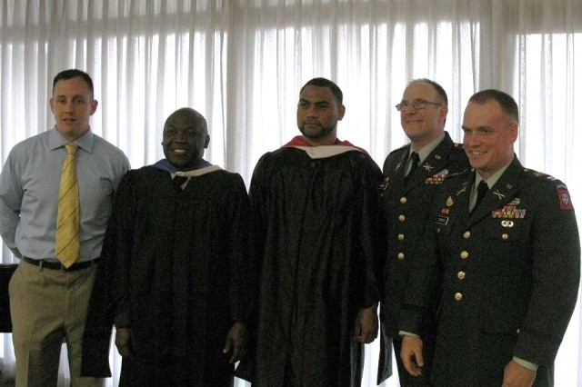 Rob Laurent, Ari Jean-Baptiste, Wes Fine, Timothy Hornik, and Gates Brown at a reception in their honor.  The five were among a group of six wounded warriors to graduate Sunday from the University of Kansas with master's degrees as part of the Wounded Warrior Education Incentive.