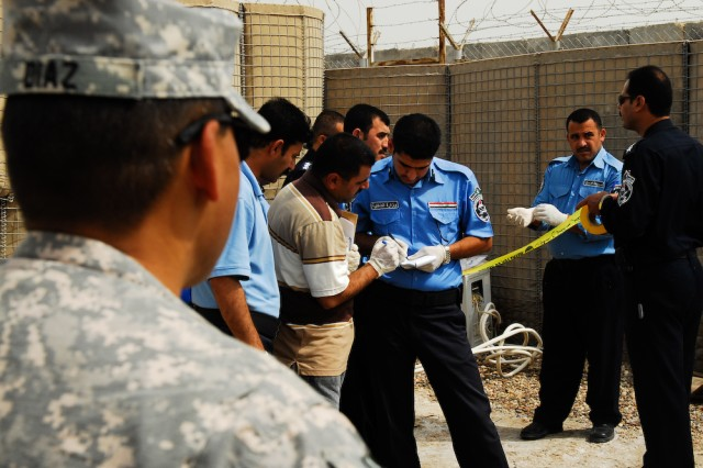 David Diaz (left foreground), a law enforcement professional assigned to the 203rd Military Police Battalion, evaluates Iraqi Police crime scene investigation procedures during a two-week evidence collection training course held on Contingency Operating Base Basra, Iraq.