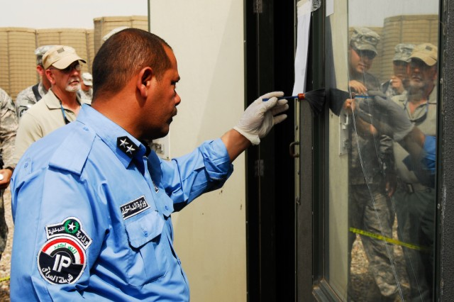 An Iraqi Police officer dusts for prints on the window of a crime scene while members of the 203rd Military Police Battalion evaluate his technique as part of a two-week evidence collection course held on Contingency Operating Base Basra, Iraq.