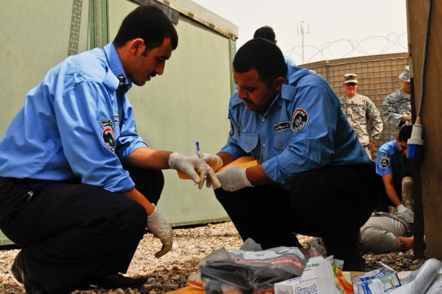 Iraqi Police officers document pieces of evidence found in a simulated crime scene using techniques learned during a two-week evidence collection course held by the 203rd MP Bn. at the Provincial Joint Coordination Center in Basra, Iraq.