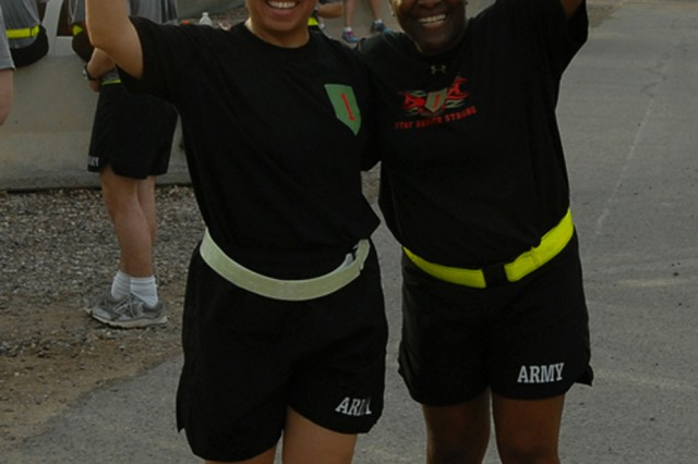 Maj. Christine Pacheco, Equal Opportunity Program manager for the 1st Infantry Division and a Manhattan, Kan. resident, poses with Sgt. 1st Class Tracy Jordan, equal opportunity advisor for the 1st Infantry Division and a St. Louis native, moments after completing the Sexual Assault Prevention 8K run held April 17, 2010, at Contingency Operating Base Basra, Iraq.