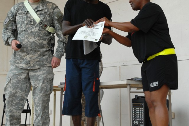 Isiah Mamai, a guard with security firm Saber International at Contingency Operating Base Basra, Iraq, and native of Kenya, receives a t-shirt and certificate of completion from Sgt. 1st Class Tracy Jordan, equal opportunity advisor for the 1st Infantry Division and a St. Louis native, as Master Sgt. Thomas Miskevish, 1st Inf. Div. sexual assault response coordinator and a native of Charleston, W.Va., looks on at COB Basra, April 17, 2010. Mamai was the overall winner of the Sexual Assault Prevention 8K run held April 17 at COB Basra, with a time of 27:10.
