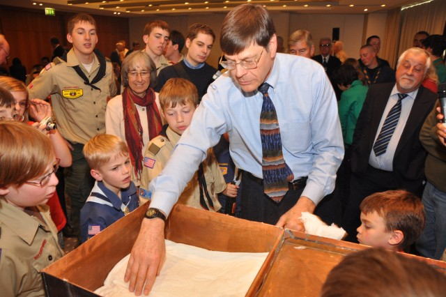 Bob Hemm, a member of Troop 11 in 1961, examines items in a time capsule placed by the Wiesbaden Scout Troop that year.