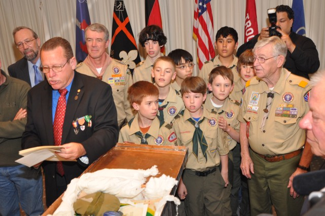 Former Scouts from Troop 11 and current Scouts from Troop 65 look at items placed in a time capsule by the former Scouts 50 years earlier at a Wiesbaden hotel.