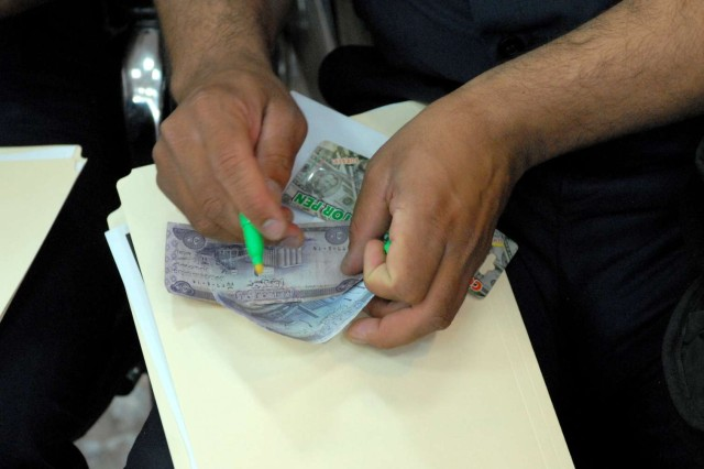 An Iraqi officer tests the chemical composition of both real and fake currency during an anti-counterfeiting class being taught by the 3212 Tactical Psychological Operations Detachment, 318th PSYOP Company, 16th PSYOP Task Force, which is attached to the 3rd Brigade Combat Team, 4th Infantry Division, at the Provincial Joint Command Center in Nasiriyah, Iraq, April 25, 2010. Most authentic currency is starch-based, while most counterfeit money is wood-based. In order to identify the chemical compound of questionable bills, special markers are used. When an authentic bill is marked, the line is barely visible. On the other hand, if the bill is a fake, then the line will turn dark.