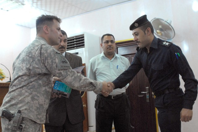 Staff Sgt. Richard Thompson, of Waterford, Wis., team leader, Tactical Psychological Operations Team D, 3212 Tactical PSYOP Detachment, 318th PSYOP Company, 16th PSYOP Task Force, gives a handshake to an Iraqi policeman during the conclusion of an anti-counterfeiting class being taught by the 3212 TPD, which is attached to the 3rd Brigade Combat Team, 4th Infantry Division, at the Provincial Joint Command Center in Nasiriyah, Iraq, April 25, 2010. The class covered a variety of topics such as the effects that counterfeiting has on an economy, the security features of modern currency, and the importance of raising public awareness.