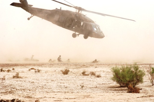 Iraqi troops watch a UH-60 Black Hawk helicopter lift-off during their final exercise in the air assault training class on Contingency Operating Base Adder, Iraq, April 22, 2010. The Iraqi Commandos and Tactical Security Unit personnel trained in exiting and entering an aircraft in a combat situation, a necessity for quick operations.