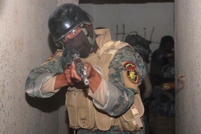 An Iraqi Tactical Support Unit soldier guards a hallway as Iraqi Commandos and TSU troops clear a building in a final training exercise for the air assault course on Contingency Operating Base Adder, Iraq, April 22, 2010. The training helps the Iraqi forces take security for the county into their hands as the drawdown of U.S. forces continues throughout Iraq.