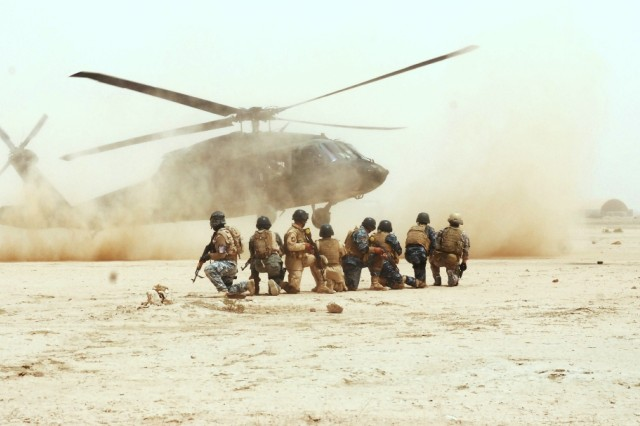 Commandos and Tactical Security Unit personnel line up as a UH-60 Black Hawk touches down to extract them from the training area during the air assault training on Contingency Operating Base Adder, Iraq, April 22, 2010. Though the training is conducted with U.S. helicopters, the tactics translate to the helicopters used by Iraqi forces.