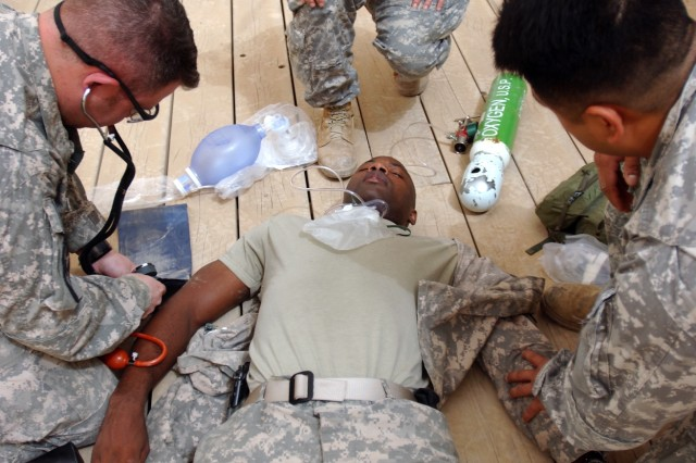 CAMP LIBERTY, Iraq - Medics gather around Sgt. 1st Class Romond Davis, the brigade surgeon cell noncommissioned officer in charge, playing the role of a collapsed patient during a combat medic sustainment course. Members of 422nd Civil Affairs Battalion conducted the week-long training for 4th Stryker Brigade Combat Team, 2nd Infantry Division medics as a way to hone their skills and instruct others after they redeploy stateside. (U.S. Army photo by Sgt. Bryce Dubee, 4th SBCT PAO, 2nd Inf. Div., USD-C)