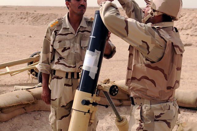 BAGHDAD - An Iraqi Field Artillery School and Directorate student loads a mortar during a live-fire exercise May 11 at QaQa range southwest of Mamhudiyah as an Iraqi officer oversees his performance. The exercise was the final task before graduating from the four-week light battery artillery course. The completion of the course demonstrates the soldiers' competence, capability and professionalism, which will serve to protect the Iraqi population. (U.S. Army photo by Staff Sgt. Samantha Beuterbaugh, 366th MPAD, USD-C)