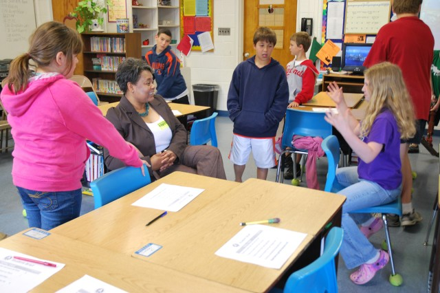 Andrea Green-Orr, Defense Access Road Program engineer, talks with students at Albers Elementary School in Albers, Ill. Green-Orr coordinated the Transportation Engineering Agency team's visit after having had similar opportunities to see the result of an education in math and science as a young student in East St. Louis, Ill.