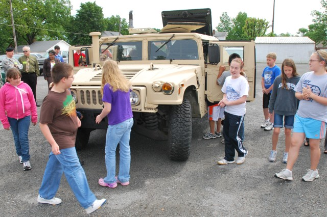 Students from Penny Angeli's (right) fifth grade class at Albers Elementary School in Albers, Ill., get a first-hand look at a humvee brought to their school as part of a visit by members of SDDC's Transportation Engineering Agency. TEA serves all of DOD, providing transportation engineering, policy guidance, research and analytical expertise to support the National Military Strategy.