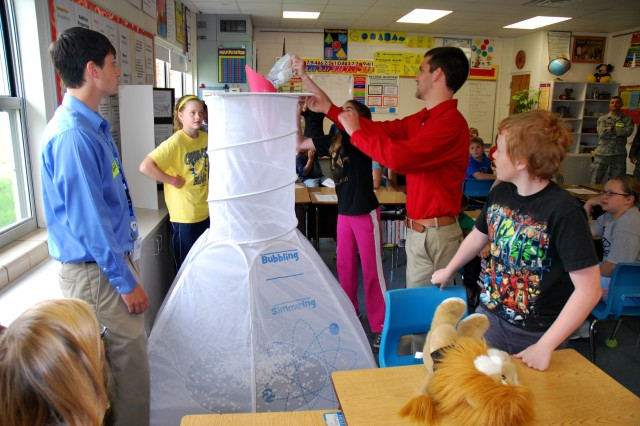Transportation Engineering Agency interns Jonathan Albers and Nathan Fuhller help Albers Elementary School students conduct an experiment demonstrating throughput, the volume and speed at which cargo can be moved through a port, using a giant test tube, a funnel and marshmallows.