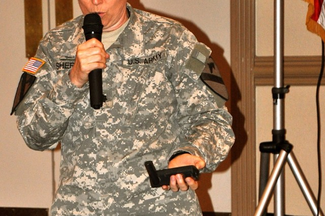 """FORT HOOD, Texas-Chaplain (Lt. Col.) Barbara Sherer, a Springfield, Mo. native, chaplain for the 1st Cavalry Division, holds her outdated GPS system which helped her to get through Iraq during a tough time. She related using her GPS to the theme of the luncheon, """"Move with a Purpose""""."""
