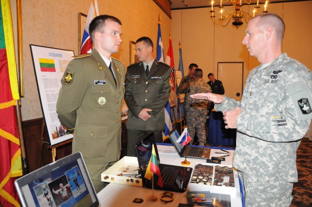 Lithuanian Capt. Vaidotas Vaicius, left, talks to 2nd Lt. Chris Fuller, Company A, Training Support Battalion during reception for international military students and their sponsors May 11 at the Officers' Club. The students educated visitors about their countries with displays, videos and food.