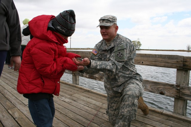 FORT CARSON, Colo.---Staff Sgt. Robert Mathis, a Warrior Transition Unit Soldier, hands Devin King, a 7th grader from Janitell Junior High School, the fish King just reeled in.