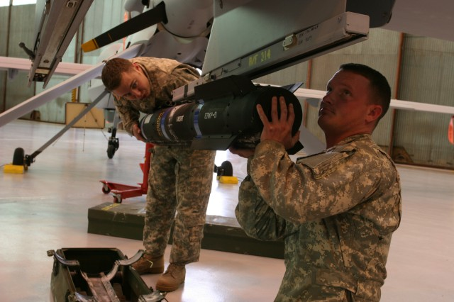 Sgt. Michael Arons (left) and Staff Sgt. Eric Wheeler, Unmanned Aircraft System Training Battalion, Company C, inspect a Hellfire simulation training missile on a Gray Eagle UAS.