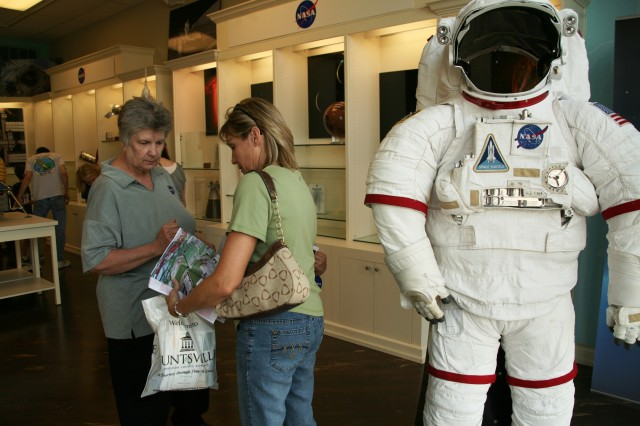 "May Wales, Marshall Space Flight Center, provides materials to an atendee at the NASA station during ""Behind the Gates of Redstone Arsenal"" at Bridge Street Town Centre on May 15."