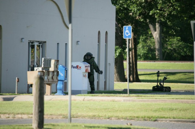 Capt. Clinton Shelby, 761st Explosive Ordnance Disposal unit, trails communications wire in front of the Fort Sill Post Office. With the unit's robot standing watch, Shelby was checking a suspicious package in the facility Thursday morning. After two hours, the package was found to contain women's clothing and some health and beauty supplies.