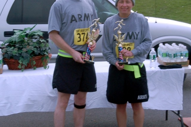 Patrick Frank, 3rd Brigade Combat Tem commander, and Laura Wells, Headquarters and Headquarters Company, 3rd BCT, pose for a picture after receiving their trophies. Frank had the fastest time among males and Wells had the fastest time among females.