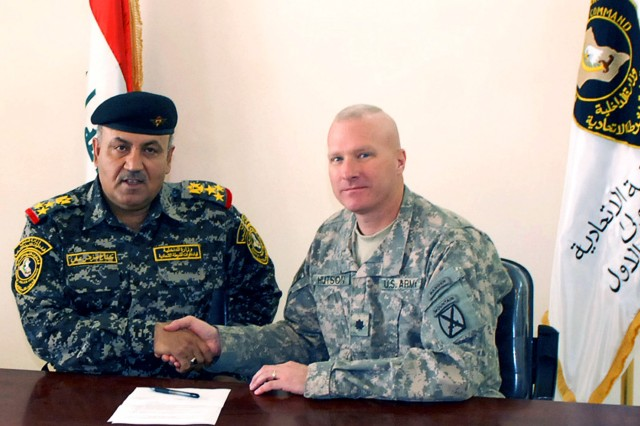 Lt. Col. Heyward Hutson, commander of 2nd Battalion, 15th Field Artillery Regiment, 2nd Brigade Combat Team, 10th Mountain Division, and Brig. Gen. Kefah Melher Ali Al-Saraj, commander of 1st Brigade, 1st Iraqi Federal Police Division, shake hands after completing the signing of documents transferring Joint Security Station Zafaraniya to the Iraqi security forces May 10.