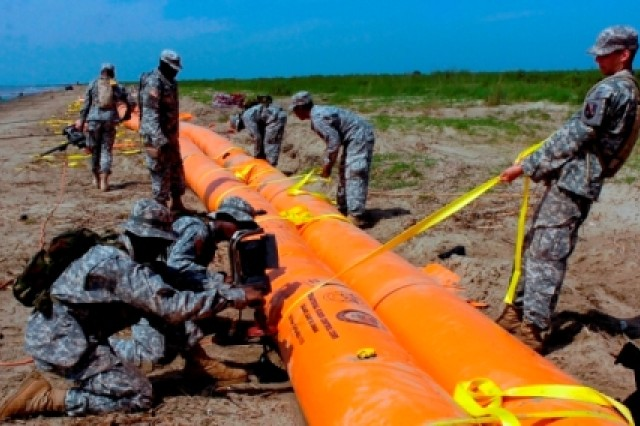 Louisiana National Guard Soldiers anchor and strap down tubing for a shoreline protection system in the southwest pass of the Mississippi River delta near Venice, La., May 18, 2010.