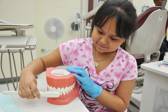 Leslie Corrales, a third grader with Varnett Elementary School in Houston, practices cleaning teeth during a visit to the dental clinic at Army Medical Department Center & School.