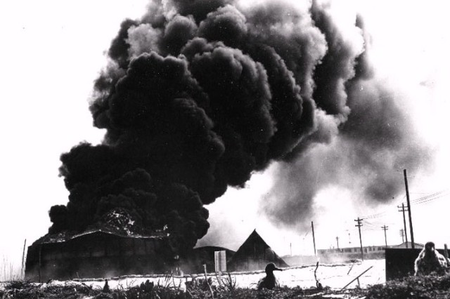 Oil tanks burn at Midway after Japanese attack, June 4, 1942.